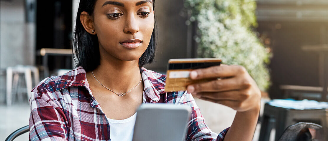 Woman holding mobile phone and credit card